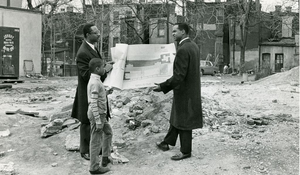 Rev. Walter Fauntroy (right), founder of the Model Inner City Community Organization reviews redevelopment plans with architect Herbert McDonald and a young boy Cedric Carter, age 9, in 1969.