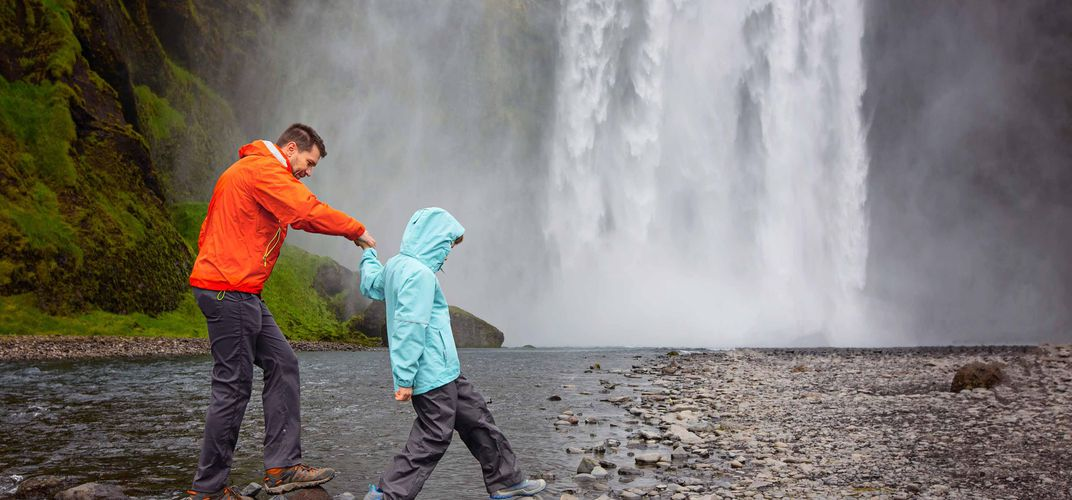 Father and son exploring a waterfall