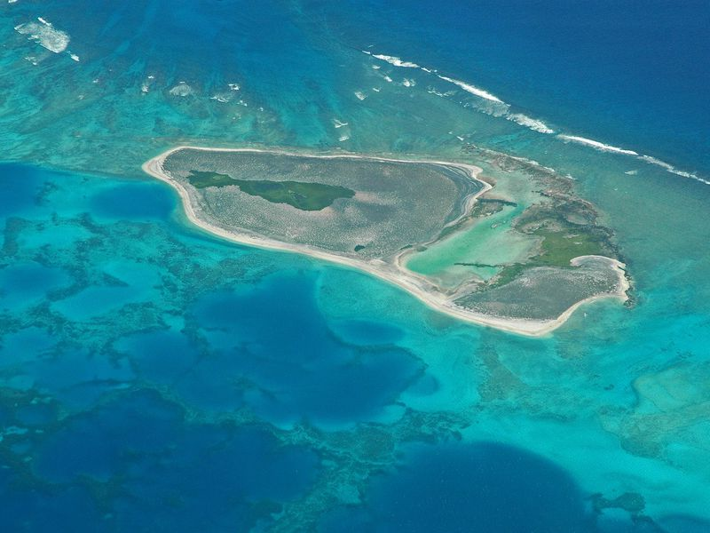 An aerial image of an atoll in the Pacific Ocean. The water is marbled green and blue, and there is a blob-shaped island in the middle. It has sandy banks with green (likely plants) on the island. There are several large lagoons inside as well.