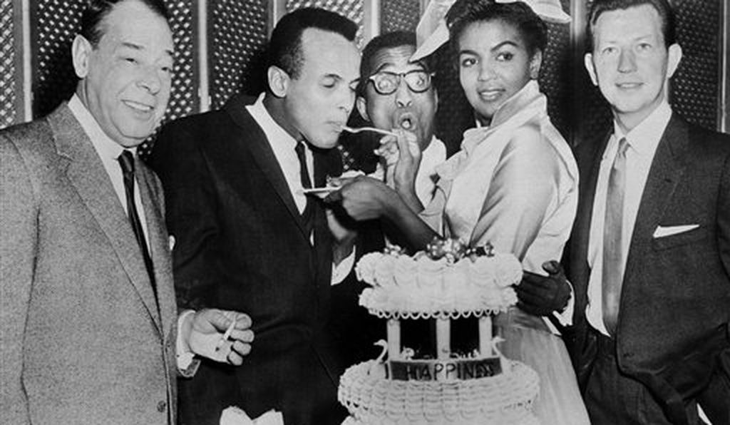 Sammy Davis Jr., 32, center glasses, and his bride, Loray White, 23, cut and serve cake to close friends and celebrities immediately following their wedding in Las Vegas, Nev., Jan. 11, 1958. The guests are, left to right: Joe E. Lewis; best man, Harry Belafonte; Davis; White and Donald O'Connor.