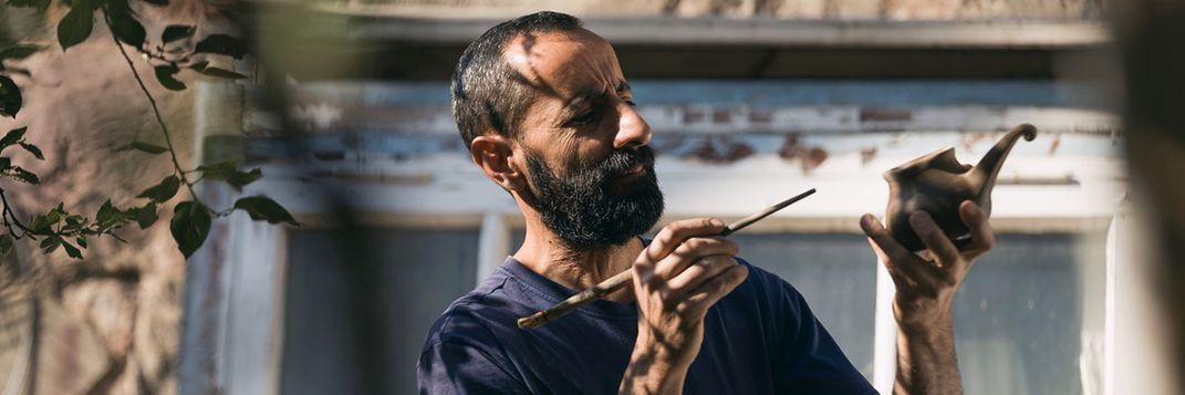 A man holds a paintbrush backwards, using the tip on the end to put finishing touches on a ladle. He holds the clay ladle in his other hand and is looking at it with a furrowed brow.