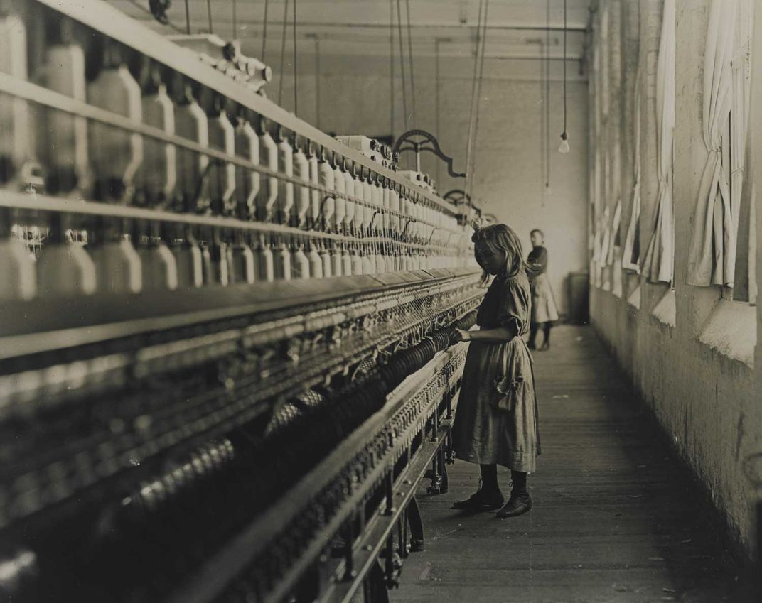 Black and white photo of young girl in a dress, working in a textile mill