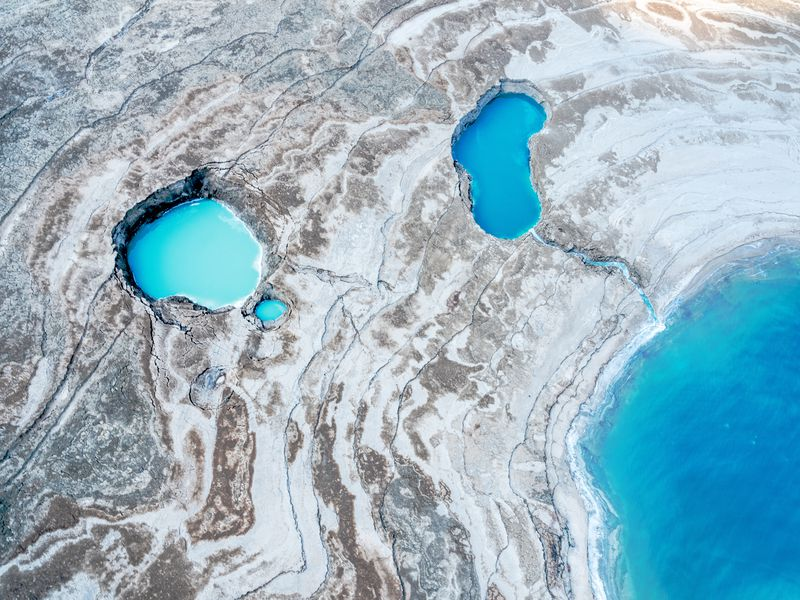 The image shows a series of sinkholes in a remote part of the land near the Dead Sea in Israel.  The area is inhabitable and very rough terrain but there is beauty and space like quality to it- especially the colors of the water pools that formed before they empty into the Dead Sea.