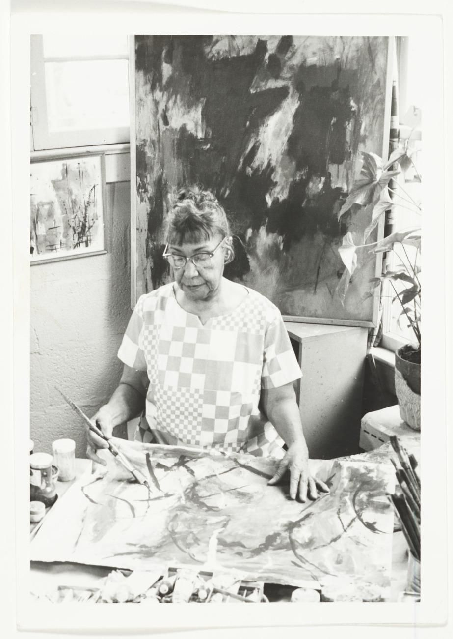 A black and white photograph of a woman in glasses painting on an unstretched canvas