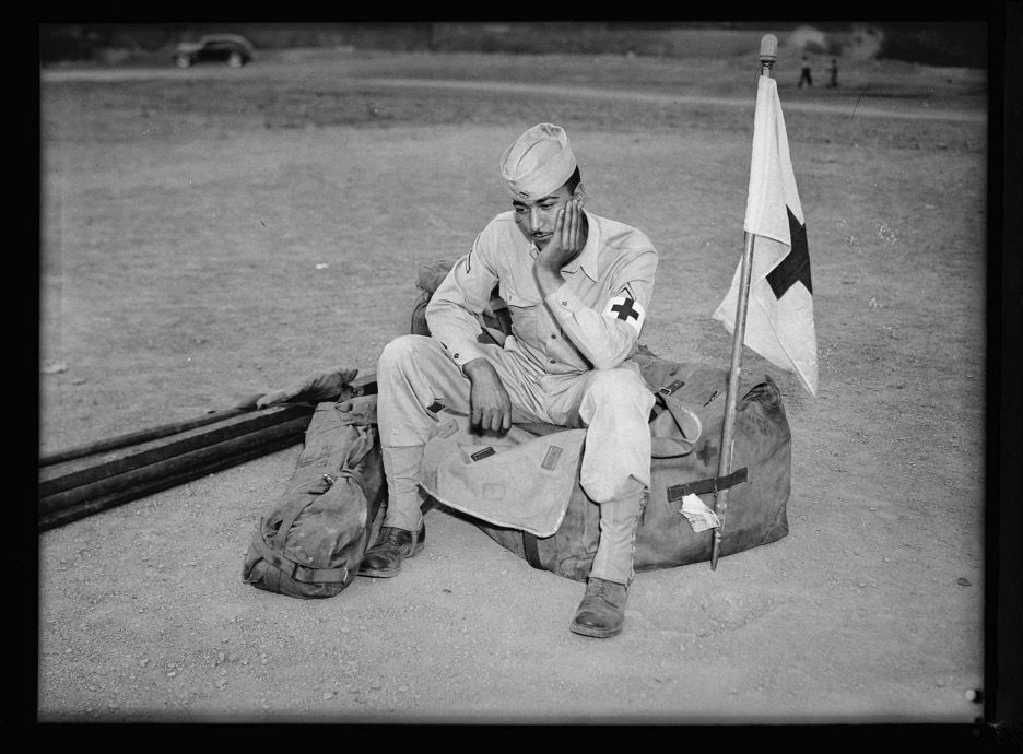 Medic soldier seated on duffel bag