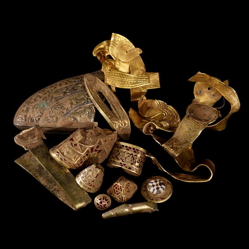 Framed against a black background, an arrangement of cuffs, jewelry and twisted gold objects inlaid with engravings