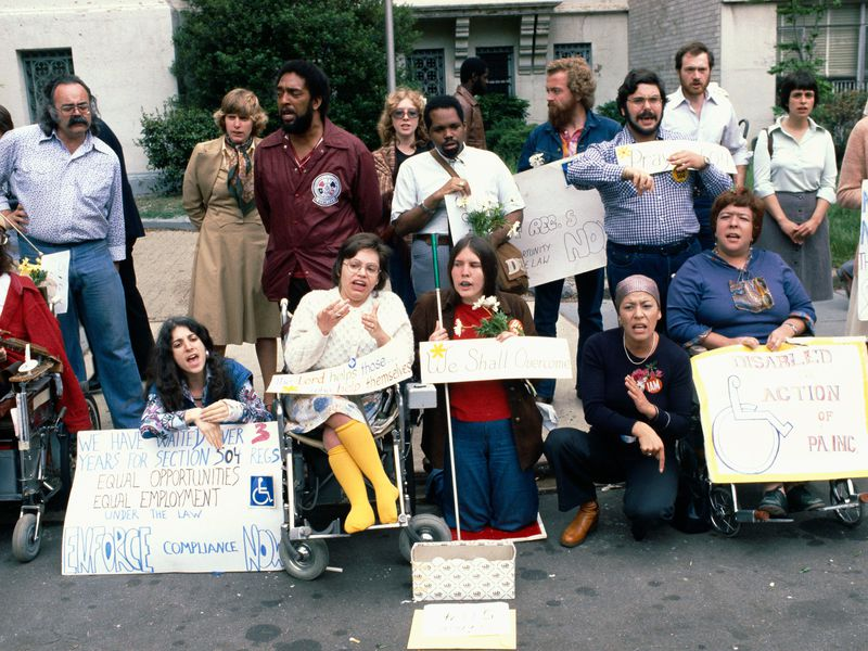 A color photograph of a group of protesters, including Judy Heumann, who is wearing bright yellow stockings. One sign reads: