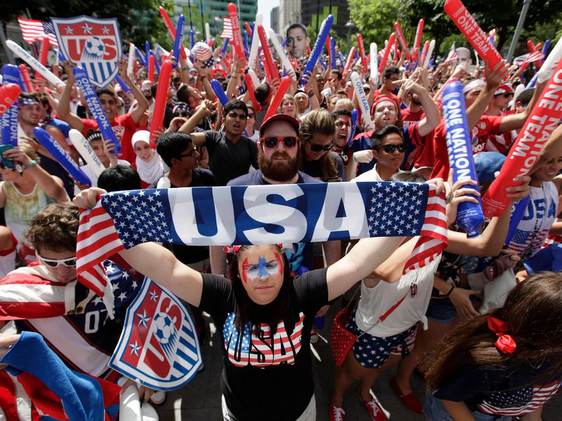 Amber Silvani holds up a USA banner as United States fans watch the 2014 World Cup soccer match