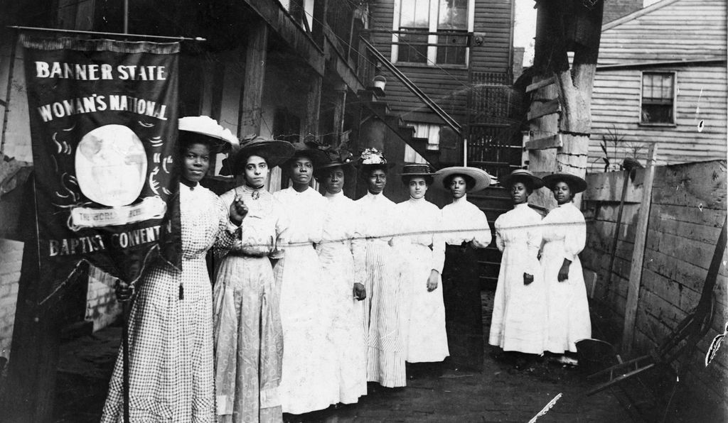 Religious leader and civil rights activist Nannie Helen Burroughs and eight other African-American women gather for the Banner State Woman's National Baptiste Convention in 1915.