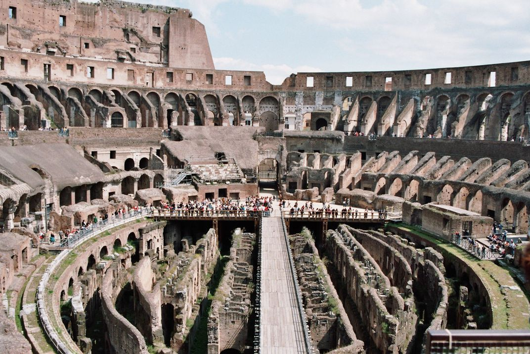 An aerial view of the Colosseum's interior, with arched walls all around; underneath where the floor used to be, a network of arches and tunnels extend far below ground