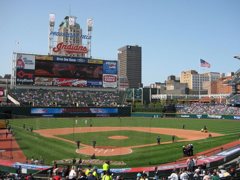 A view of a baseball field, with Indians written in red lettering above the scoreboard and crowds filling the stands