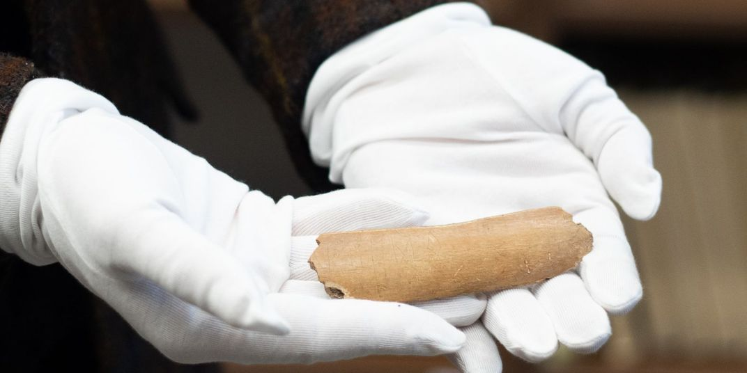Researcher holds cow bone inscribed with Germanic runes