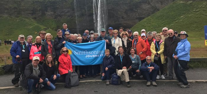 Smithsonian Journeys travelers in front of the Seljalandsfoss waterfall