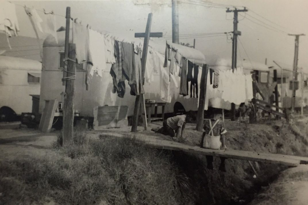 A black and white photo shows a child sitting below a clothesline in front of a row of white trailers.