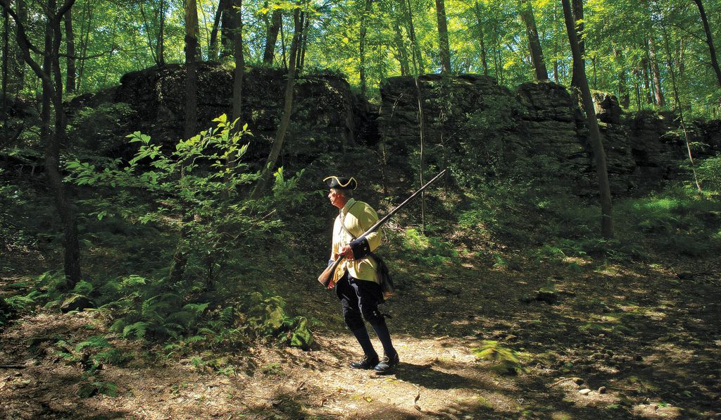A re-enactor dressed as a French marine walks through Jumonville Glen at Fort Necessity.