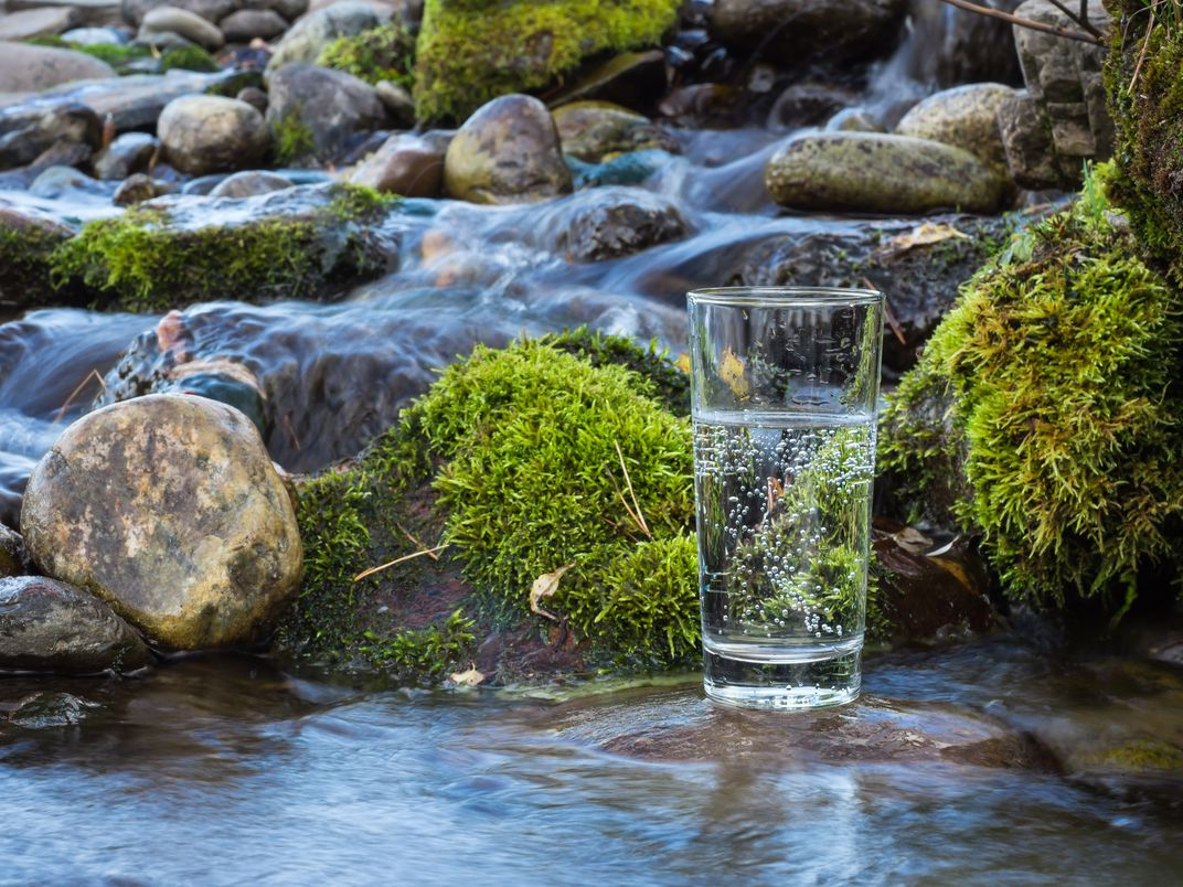 Image of glass of water by a stream