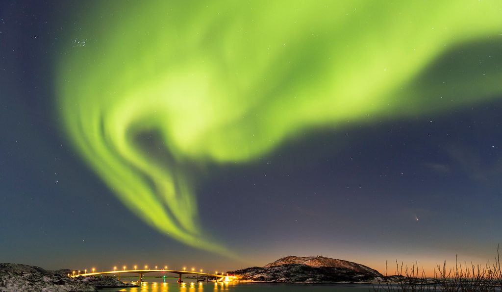 Northern Lights above a bridge and fjord near Tromsø, Norway.