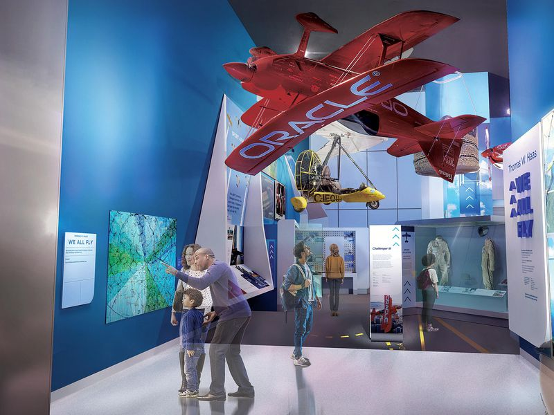 museumgoers under a red Oracle aircraft