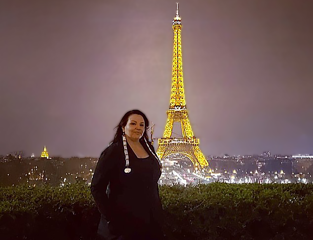 The fashion designer Norma Baker–Flying Horse, dressed in a black gown and gloves, stands outdoors in Paris at night. The Eiffel Tower is lit in the far background.