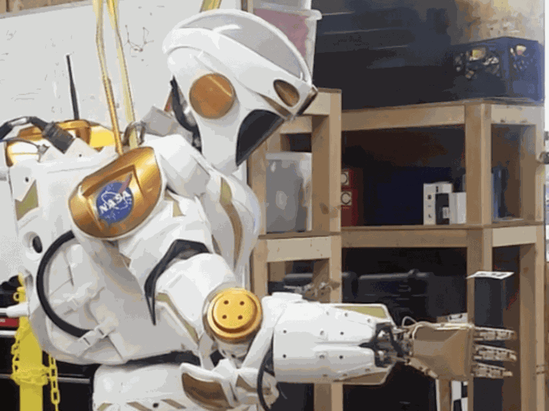 A NASA Valkyrie robot picks up an item with its hand.