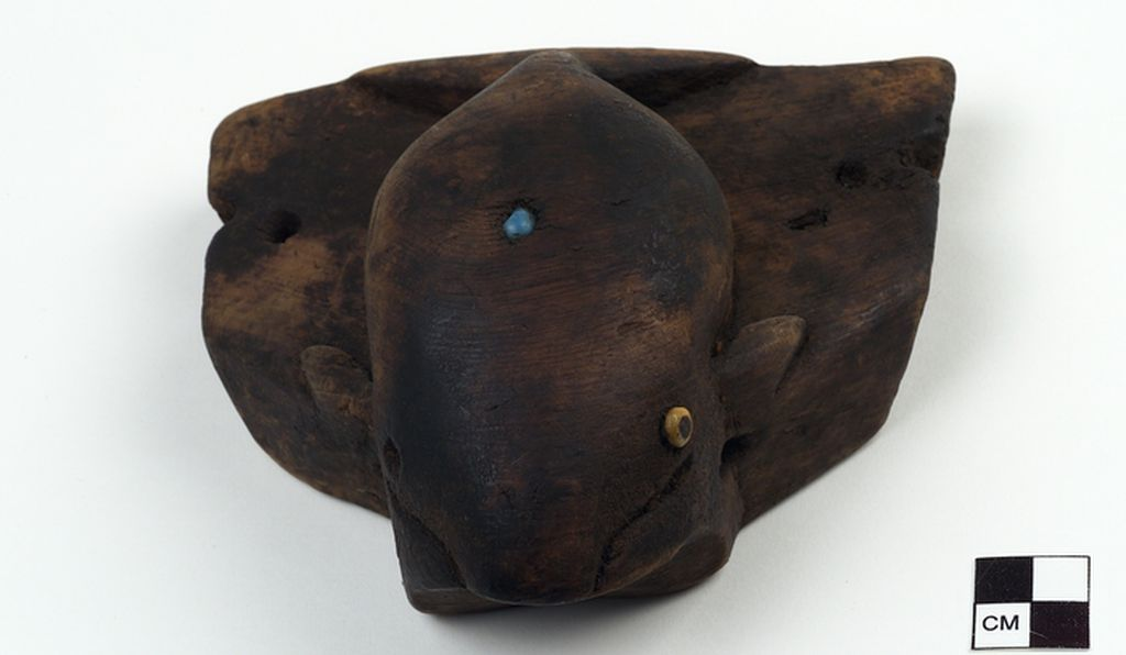 Another Umiak seat representing a whale, made of wood and inlaid with glass beads.