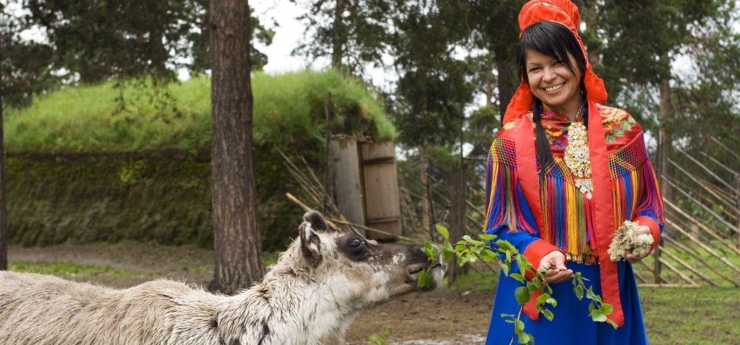 Woman in traditional Sami dress with reindeer