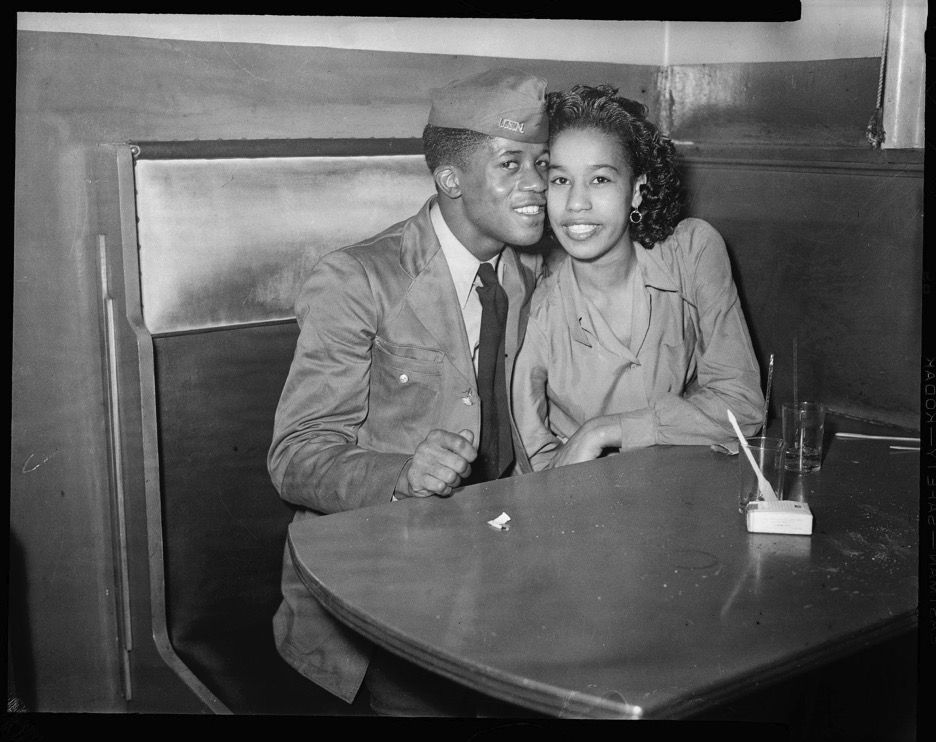 Man in military uniform and woman seated in booth