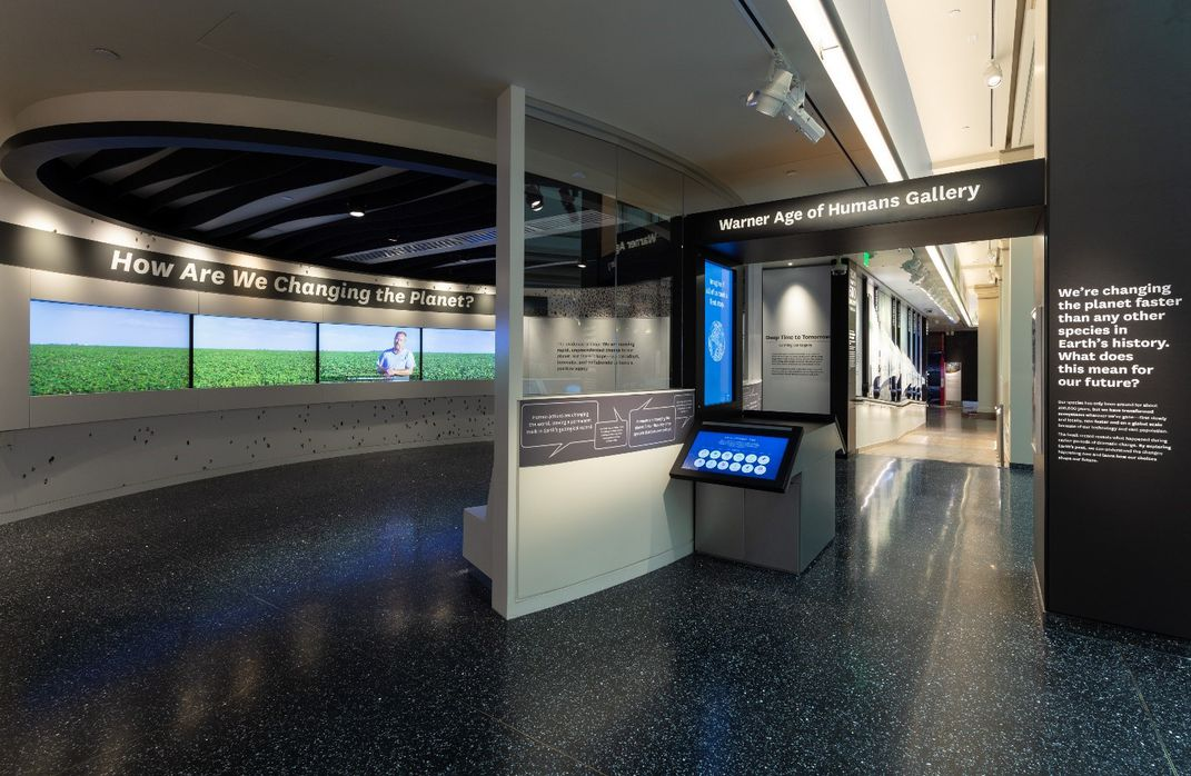 "Small theater featuring four screens and ""How Are We Changing the Planet?"" in white on a black wall at the Smithsonian's National Museum of Natural History"