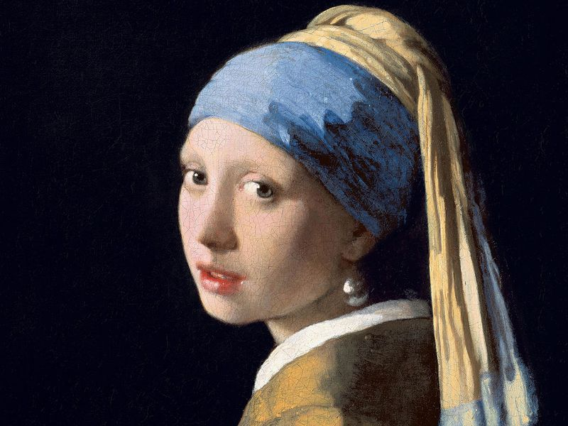 A portrait of a young white woman framed by an all-black background; she turns toward the viewer and wears a blue headscarf and one large, illuminated earring dangling from her left ear; her lips are slightly parted