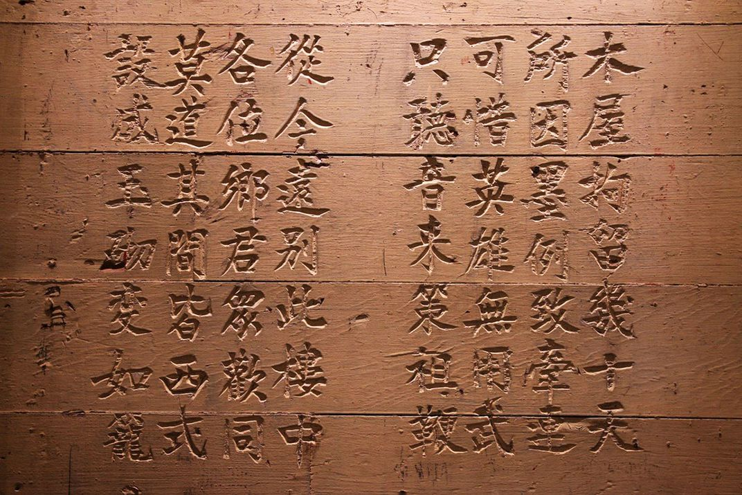Brown stone wall etched with Chinese characters.
