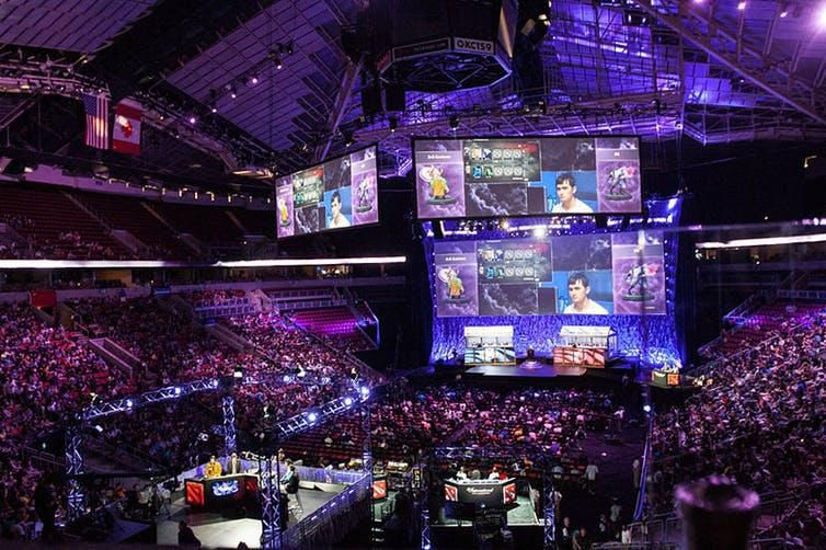 An arena packed with people watching others play video games.