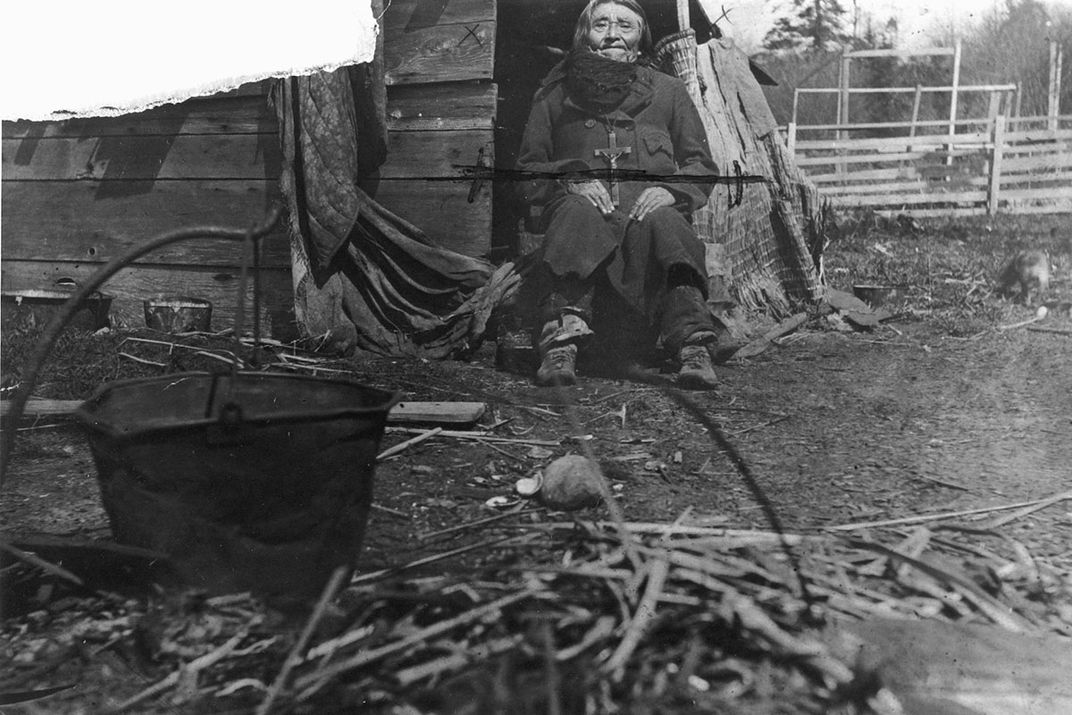 A man sits in the doorway of a wooden shack. In the foreground is an outdoor fire pit and black pot. Black-and-white archival photo.