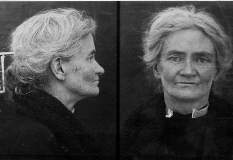 A black and white criminal mugshot of a white woman with graying hair, in a black outfit