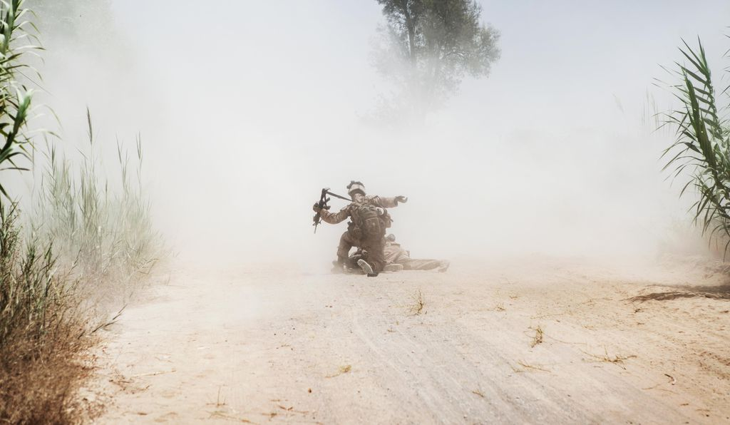 Seconds after an IED buried in the road hit Cpl. Manuel Jimenez, Cpl. Eric Hopp rushes in to help. The unit had engaged in a firefight against the Taliban earlier that same day.