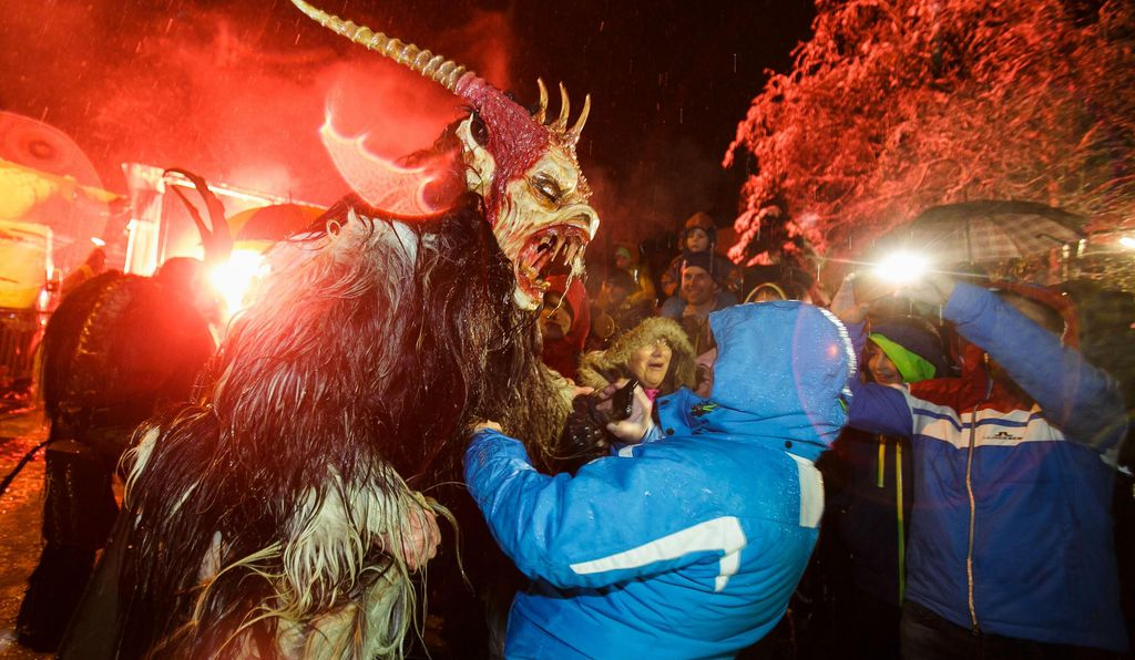 A Krampus scares an onlooker during Krampuslauf.