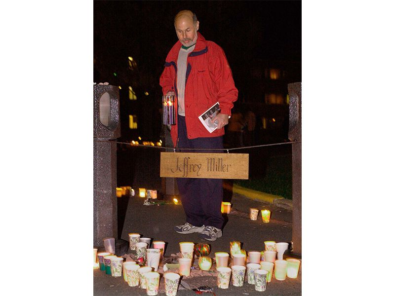 A man in a red jacket looks down at candles surrounding a sign that says 'Jeffrey Miller'