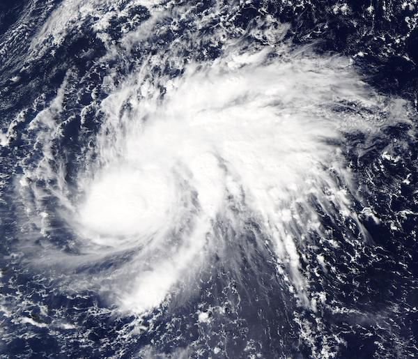 A satellite photo of Super Typhoon Goni. It shows Goni, a large, white, swirling storm moving over the blue Pacific ocean