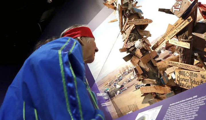 John Richard Edwards (Onondaga) takes part in the installation of the mile-marker post from the Dakota Access Pipeline in the exhibition