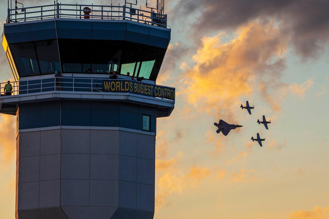 Raptor and Mustangs by a control tower