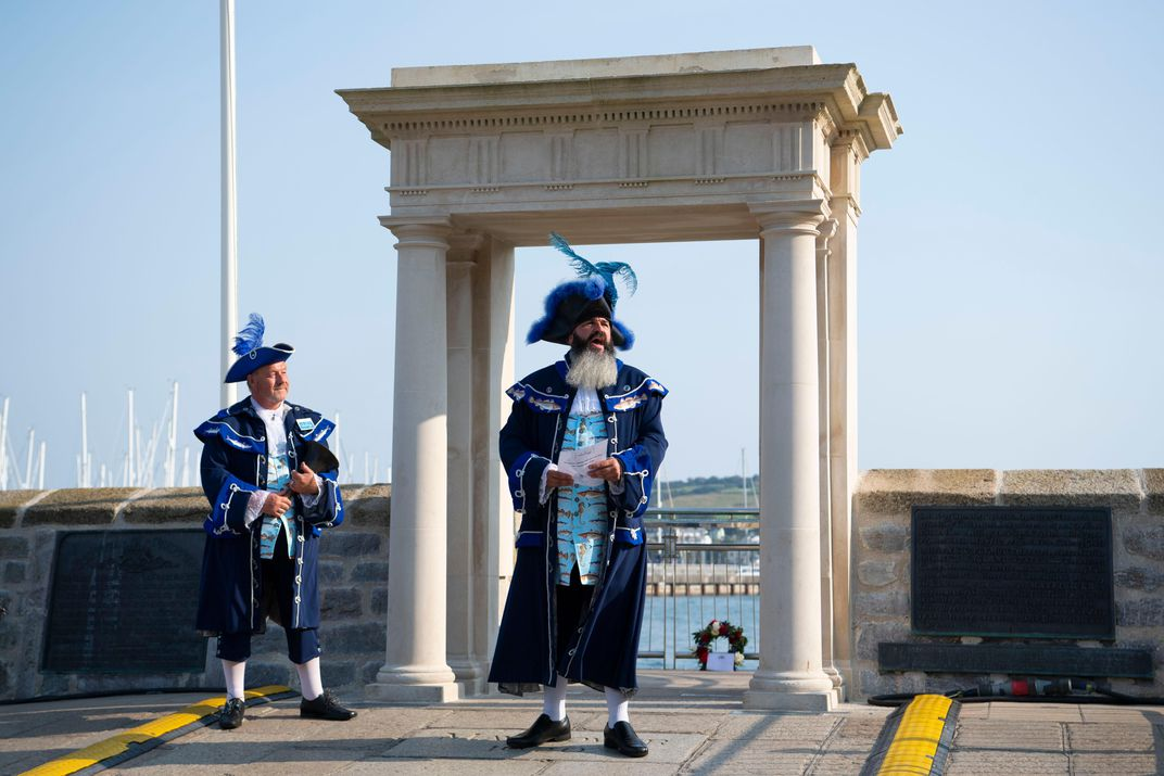 Two men in period costume, with blue feathers in their caps, speak in front of a neoclassical square archway that marks the spot where the Pilgrims set off for America, 400 years ago
