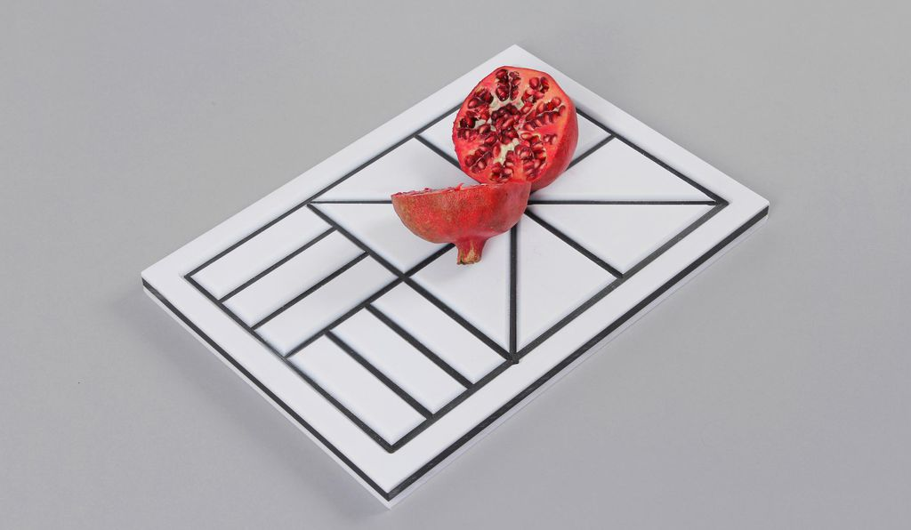 A white cutting board, scored with black grooves, by Simon Kinneir, helps people with low vision.