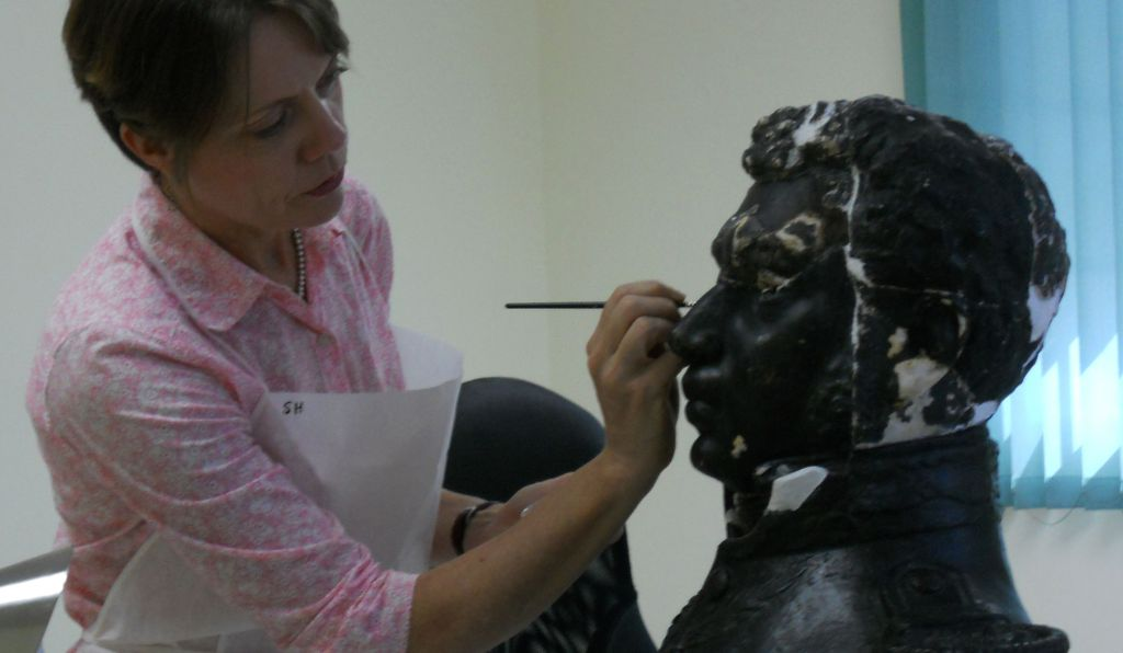 Stephanie Hornbeck inpaints losses on bust of Alexandre Petion from the collections of MUPANAH.