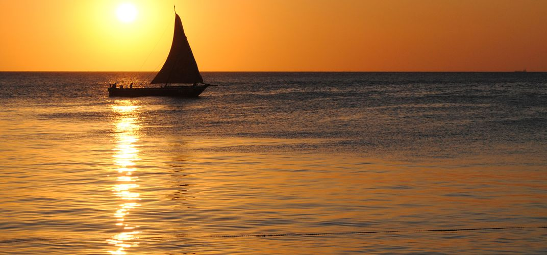 Sunset with traditional <i>dhou</i> on the water off Zanzibar's Stone Town
