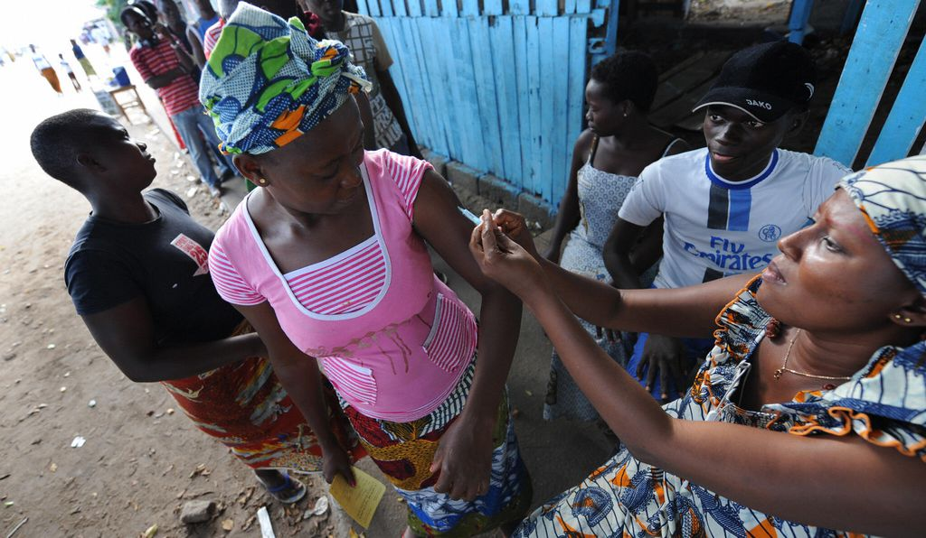 A health worker administers a yellow fever vaccine to a woman on August 27, 2008 on a roadside in Koumassi, a poor quartier of Abidjan after a case was discovered of yellow fever.