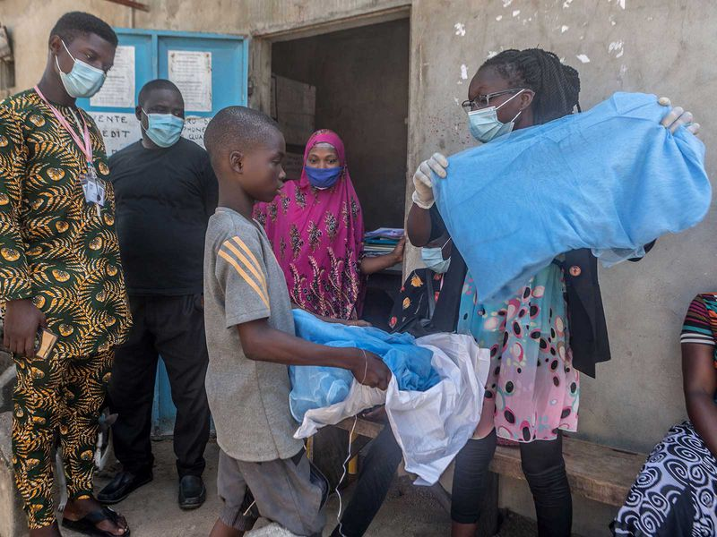 Handing out bed nets in West Africa