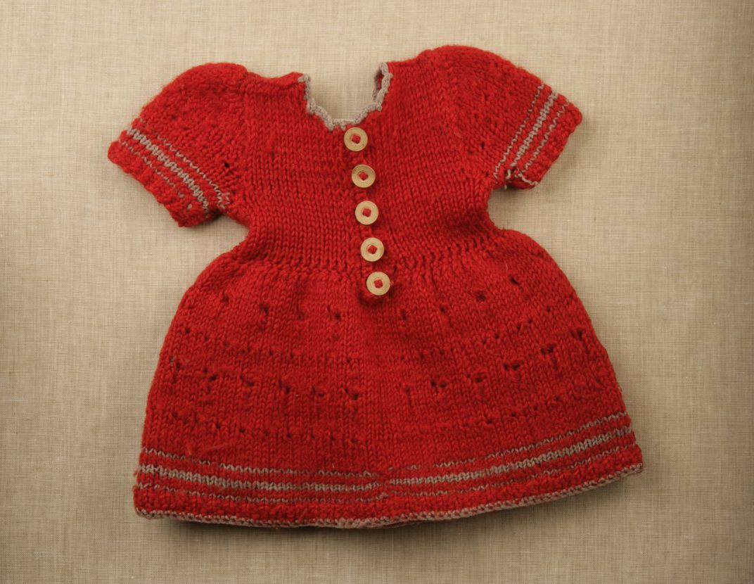 A small red dress with white buttons and gray edging