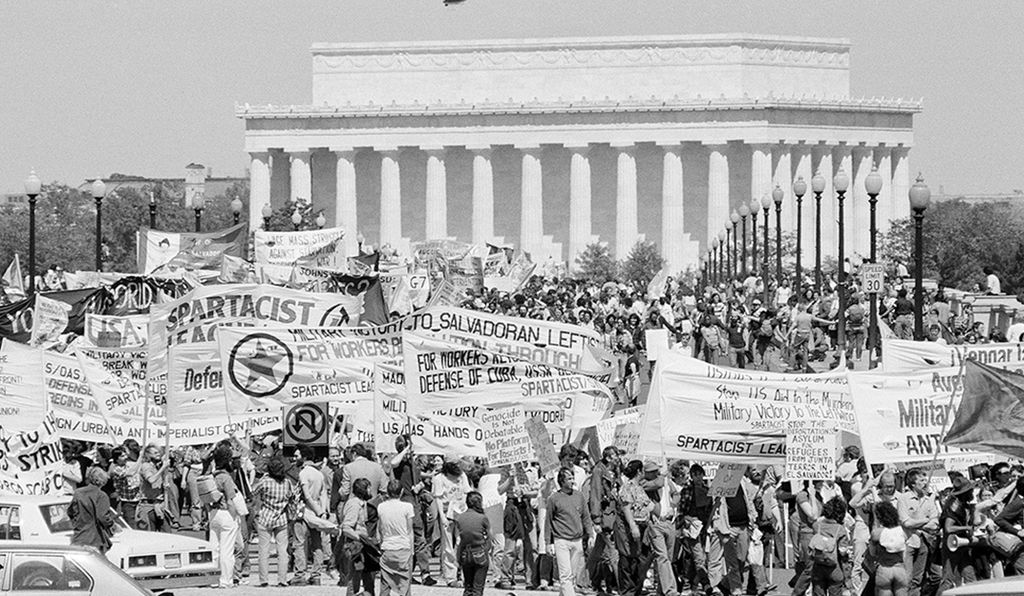 With the Lincoln Memorial in the background, anti-war marchers cross the Memorial Bridge on their way to the Pentagon for a rally to protest U.S. military involvement in El Salvador and President Reagan's proposed cuts in domestic social programs, May 3, 1981.