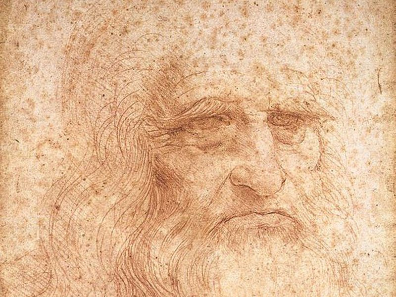 A portrait of an elderly man's face and long hair and beard, rendered in fine red chalk lines on a paper spotted with age