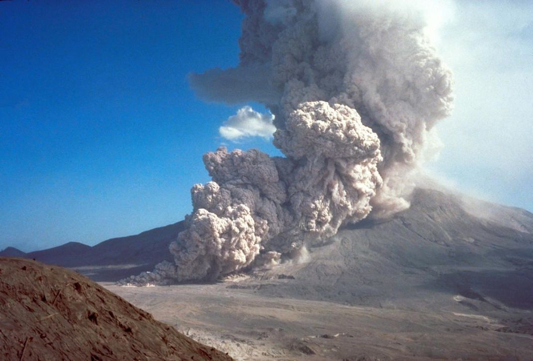 A cloud of ash and rock spews out of an erupting volcano.