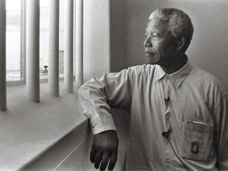 Nelson Mandela in prison looking out window